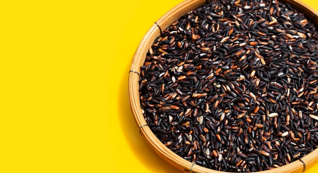 Raw black sticky rice in bamboo basket on yellow background.