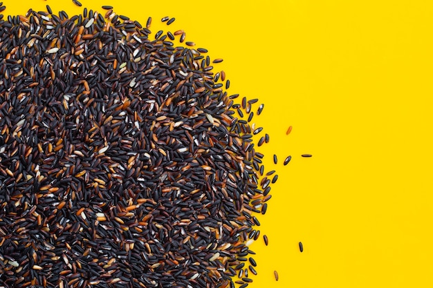 Raw black sticky rice on yellow surface