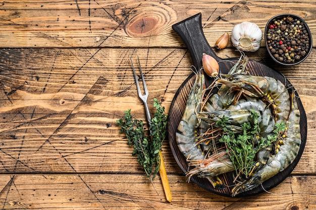 Raw black tiger shrimps prawns on a cutting board with herbs