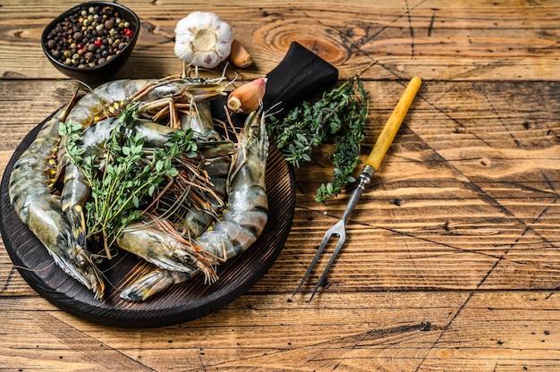 Raw black tiger shrimps prawns on a cutting board with herbs.