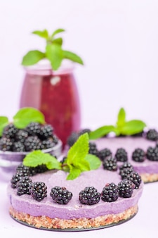 Raw blackberry dessert decorated with fresh ripe forest berries and green mint leaves