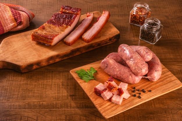 베이컨과 향신료의 신선한 큐브와 나무 보드에 원시 브라질 베이컨 소시지