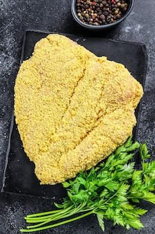 Raw breaded german weiner schnitzel.   top view.