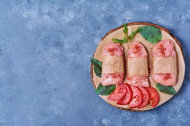 Сырое мясо грудки со специями на деревянной доске на синем