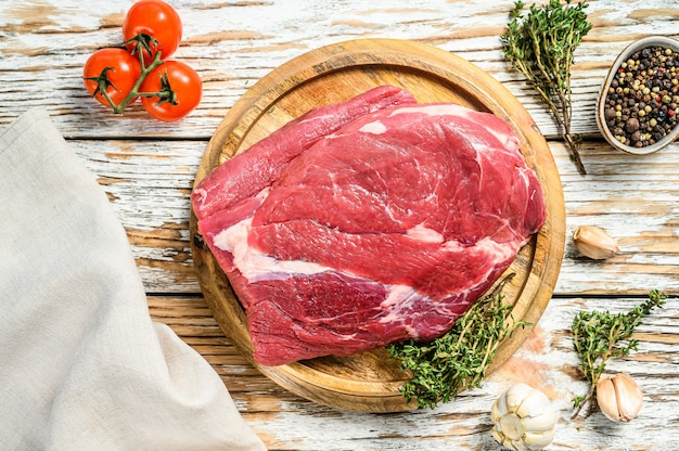 Сырые грудинки говядины вырезать на деревянной доске на черный ангус говядины на белом столе.