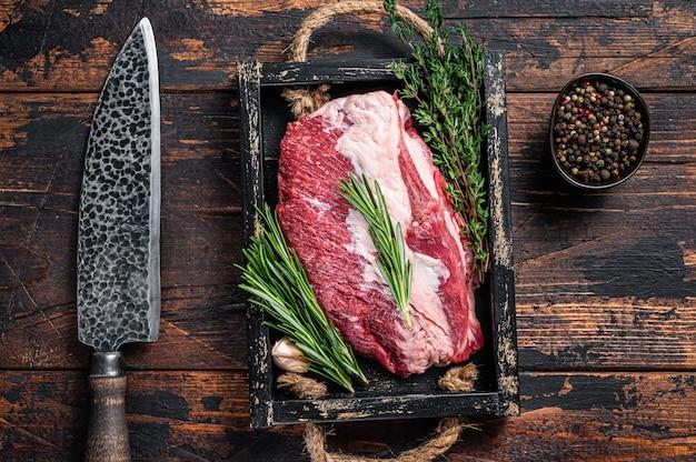Сырое мясо говядины грудинки нарезать ножом на деревянном подносе. темное дерево