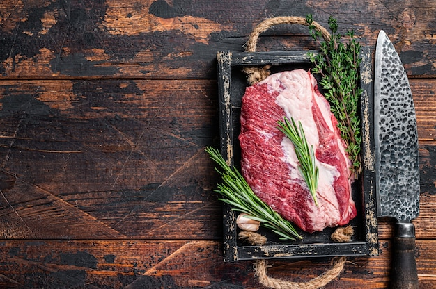 Raw brisket beef meat cut on a wooden tray with knife. dark wooden background. top view. copy space.