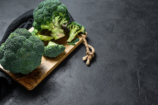 Raw broccoli in a wooden bowl. top view.
