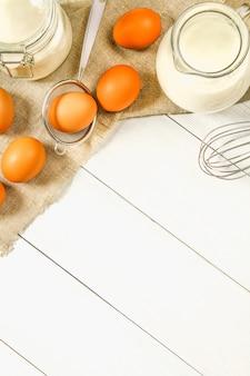 Raw brown chicken eggs, milk, sugar, flour, whisk, rolling pin
