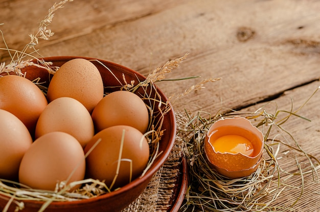 Сырые коричневые яйца на деревянных фоне
