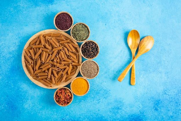 木の板の上の生の茶色の過去と青いテーブルの上の様々な種類のスパイス。