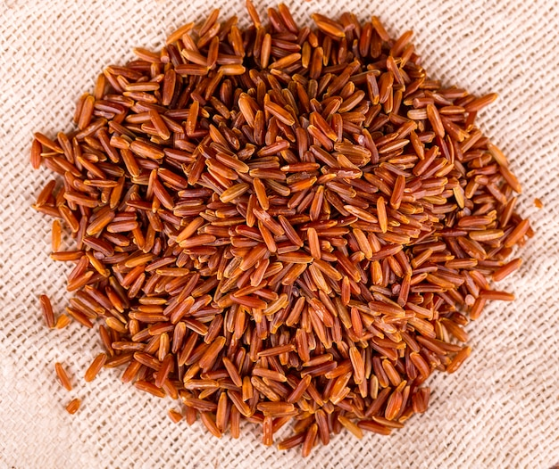Сырцовый коричневый рис l на предпосылке дерюги.