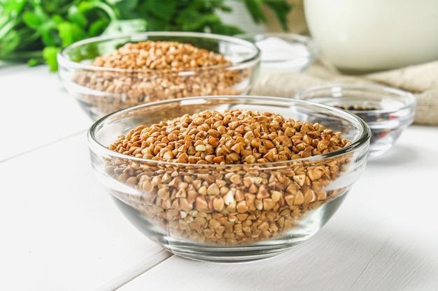 Raw buckwheat in glass bowls on sackcloth on a wooden background. healthy diet food.