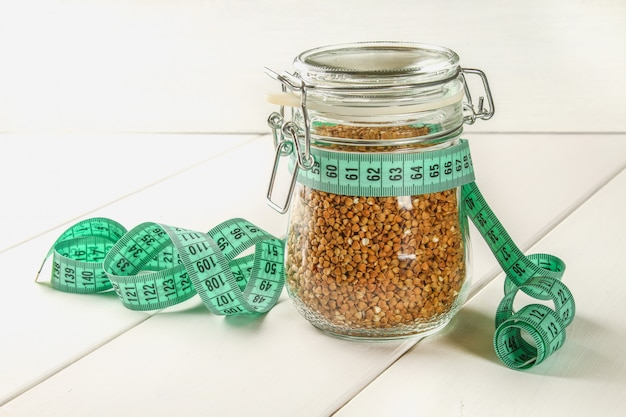Raw buckwheat in a glass jar with a centimeter on sacking on a wooden table
