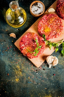 Raw burger cutlets with salt, pepper, oil, herbs and spice, on dark table,  copyspace top view