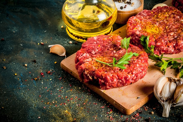 Raw burger cutlets with salt, pepper, oil, herbs and spice, on dark table,