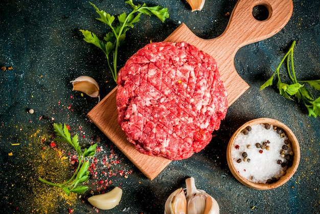 Raw burger cutlets with salt, pepper, oil, herbs and spice