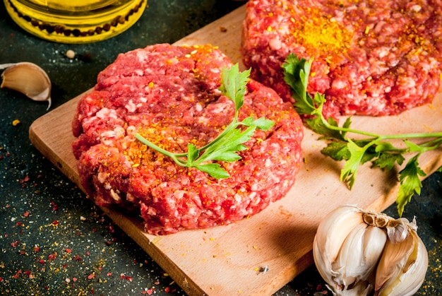 Raw burger cutlets with salt, pepper, oil, herbs and spices