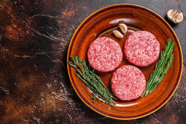 Сырые котлеты из мяса бургера с говяжьим фаршем и зеленью на тарелке