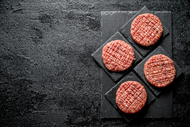Raw burgers on black stone stands. on rustic surface
