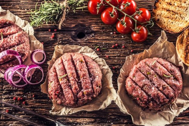 タマネギトマトハーブとスパイスと木製のテーブルの上の生のハンバーガー。