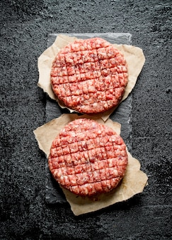 Raw burgers on paper. on black rustic background