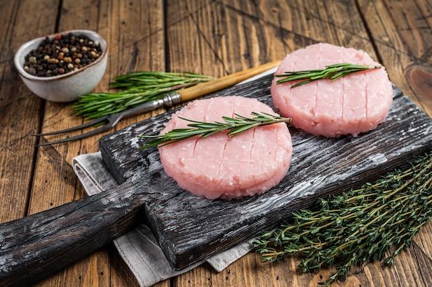 Сырые котлеты для гамбургеров из органического мяса курицы и индейки с тимьяном и розмарином. деревянный фон. вид сверху.