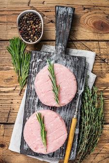 타임과 로즈마리를 곁들인 유기농 닭고기와 칠면조 고기로 만든 생 버거 패티. 나무 배경입니다. 평면도.