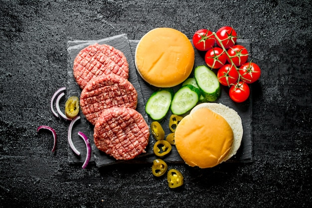 Raw burgers. preparation of burgers from beef patties, tomatoes and cucumbers. on black rustic background