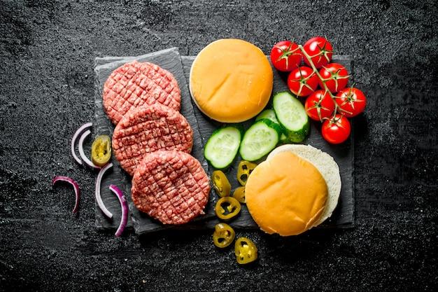 생 버거. 쇠고기 패티, 토마토 및 오이에서 햄버거 준비. 검은 소박한 배경에