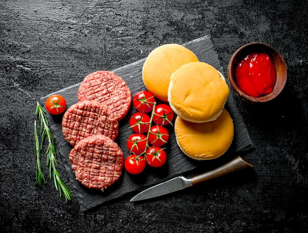 Raw burgers with cherry tomatoes, bread and rosemary. on black rustic background