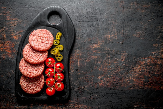 Raw burgers with jalapeno chillies and tomatoes. on dark rustic background