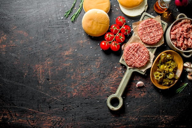 Raw burgers with jalapeno chillies, tomatoes and scones. on dark rustic background