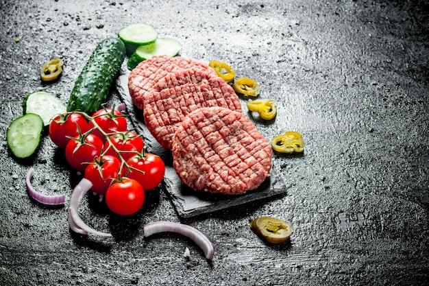 양파 슬라이스, 토마토, 후추, 오이를 곁들인 생 버거. 검은 소박한 표면에