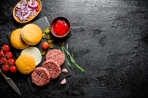 Raw burgers with tomatoes, scones, sauce and chopped onion. on black rustic background