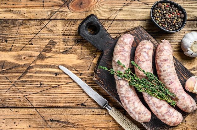 Сырые мясные колбаски в шкурах с зеленью на деревянной разделочной доске