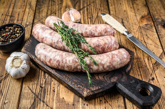 Raw butchers sausages in skins with herbs on the wooden cutting board
