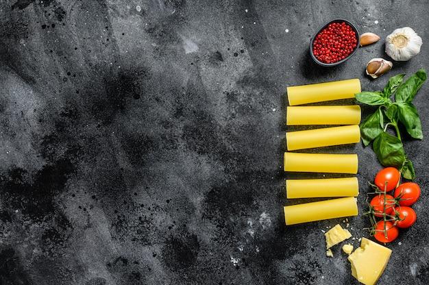 生のカネロニパスタ。イタリア料理。調理材料:バジル、チェリートマト、パルメザンチーズ、ニンニク。黒の背景。上面図。コピースペース
