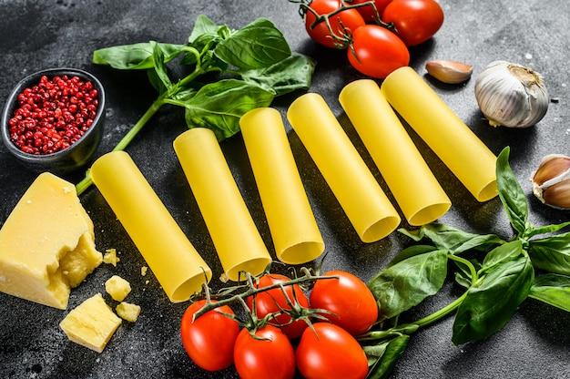 Сырье каннеллони паста. итальянская кухня. приготовление ингредиентов: базилик, помидоры черри, пармезан, чеснок. вид сверху