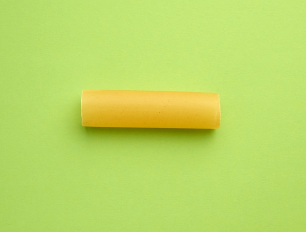 Сырые каннеллони макароны на зеленом фоне
