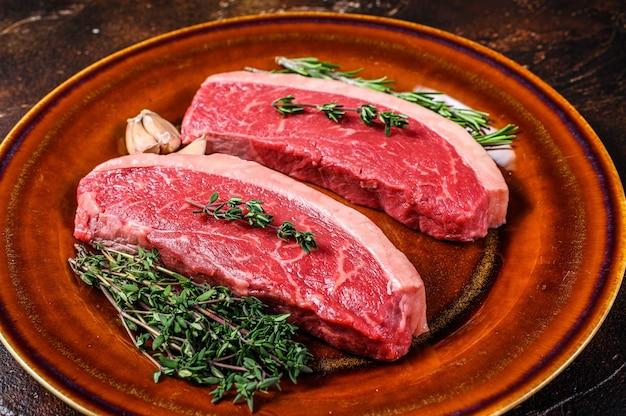 Сырой огузок крышки или бразильский стейк из говядины пиканья на деревянном столе. вид сверху.