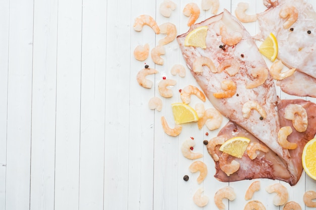 Raw carcass of squid and shrimp with spices and lemon is ready for cooking on the table.