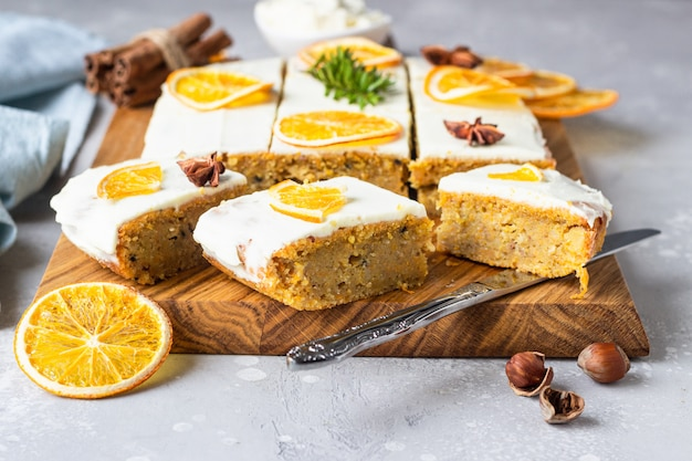 Raw carrot cake with cream cheese frosting, dried orange slices and spices (cinnamon and anise).