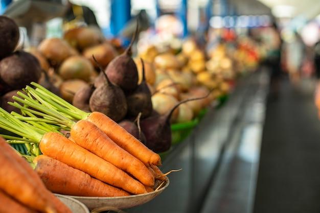 Сырая морковь и свекла на прилавке.
