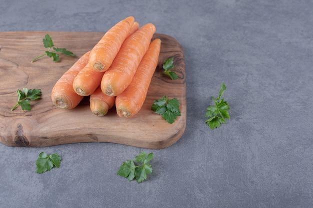 Сырая морковь с зеленью на разделочной доске, на мраморной поверхности.