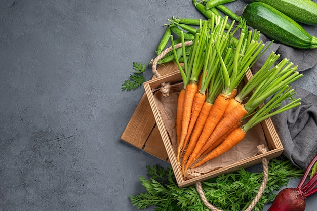 Raw carrots, zucchini and beets on a gray background. top view, copy space. natural, organic products. Premium Photo