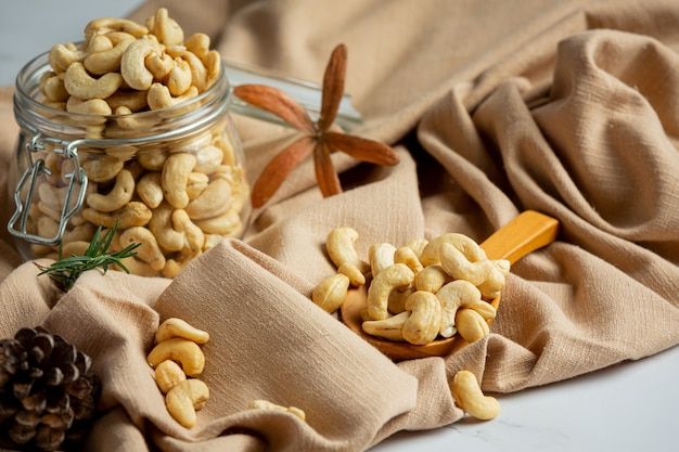 Raw cashews nuts in an open glass jar on marble background