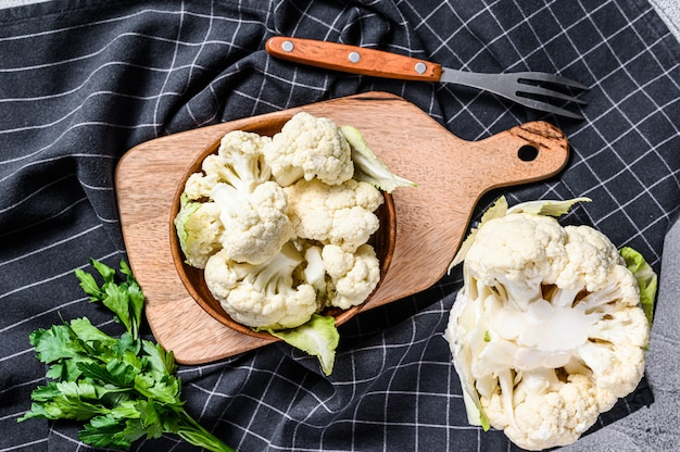 Raw cauliflower cut into pieces in wooden bowl. white background. top view