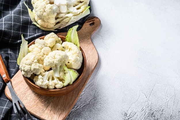 Raw cauliflower cut into pieces in wooden bowl. white background