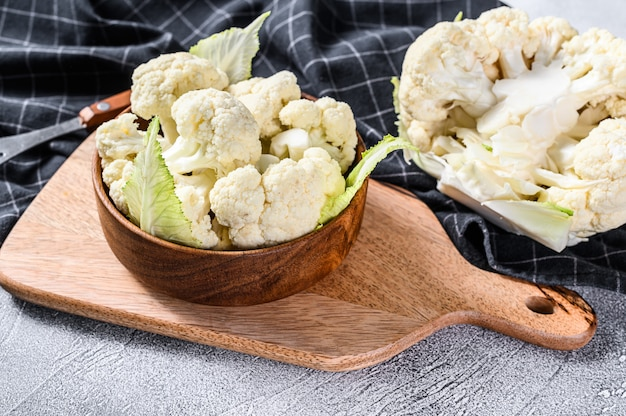 Raw cauliflower cut into pieces in wooden bowl